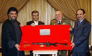 Hezbollah leader Sheikh Nasrallah (left) and his top aide, Hussein Khalil (second from left), present a gift rifle to the head of the Syrian intelligence service to Lebanon, Rustom Ghazali (far right) in April 2005, two months after the Hariri murder and only days before Syria would pull the last of its troops from Lebanon. Looking on is Gen. Fayed al-Haffar. According to UN investigators, Khalil and Col. Hassan exchanged numerous phone calls in 2004 and 2005. (Reuters photo)