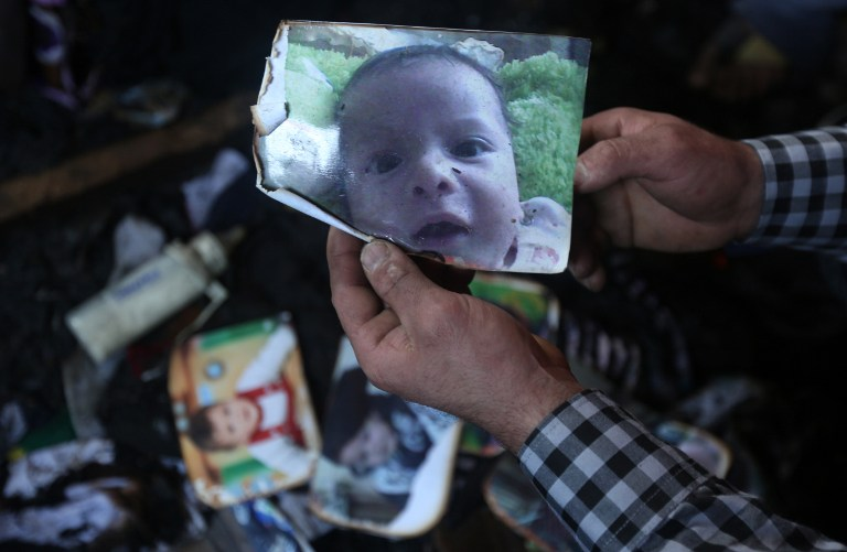 A man shows a picture of 18-month-old Palestinian toddler Ali Saad Dawabsha who died when his family house was set on fire by Jewish settlers in the West Bank village of Duma on July 31, 2015. The Palestinian toddler was burned to death and four family members injured in the arson attack on two homes in the occupied West Bank. AFP PHOTO / JAAFAR ASHTIYEH
