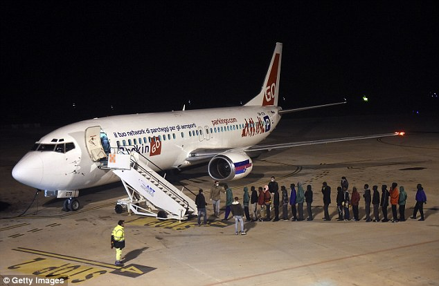 Forced to leave: Migrants wait to board a plane at Lampedusa airport in Italy, bound for a detention center elsewhere in the country
