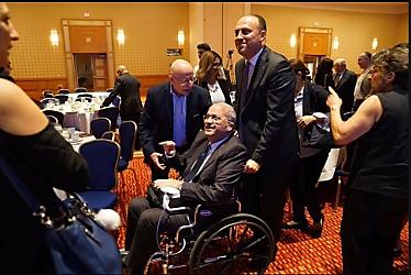Saeb Erekat en una silla de ruedas empujada por Husam Zomlot, representante de la Autoridad Palestina en Estados Unidos, en una reunión de la diáspora árabe y palestina en EEUU.