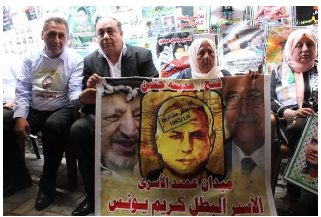 """Ibrahim Ramadan, governor of the Jenin district, next to the mother of terrorist Karim Yunes at the inauguration of the """"Karim Yunes square"""" in Jenin . They hold a sign of Karim Yunes flanked on the left by Yasser Arafat and the right by Mahmoud Abbas. The Arabic reads, """"Fatah/Jenin. Detained since January 6, 1983. The square [named for] the oldest prisoner. Prisoners and hero, Karim Yunes"""" (bukra.net, May 18, 2017)."""