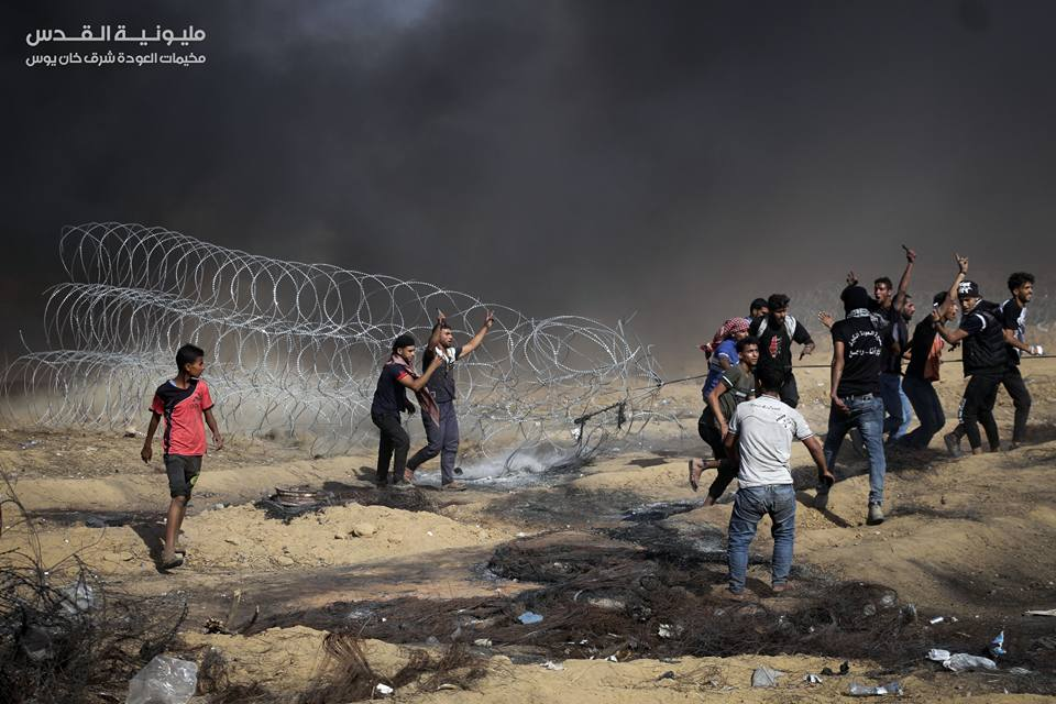 Young Gazan rioters pull at a coil of barbed wire near the security fence in eastern Khan Yunis.