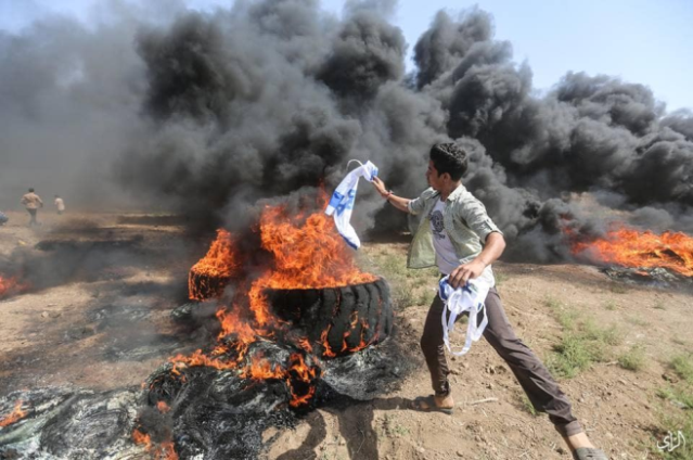 """Burning the Israeli flag (Facebook page of the """"supreme authority of the great return march,"""" June 8, 2018)."""
