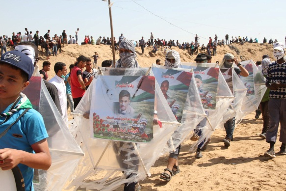 """Children carry kites with pictures of shaheeds (Facebook page of the """"supreme authority of the great return march,"""" June 8, 2018)."""